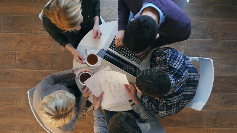 Groep zekere bedrijfsmensen die in slimme vrijetijdskleding terwijl het zitten bij het bureau in bureau samenwerken stock afbeelding