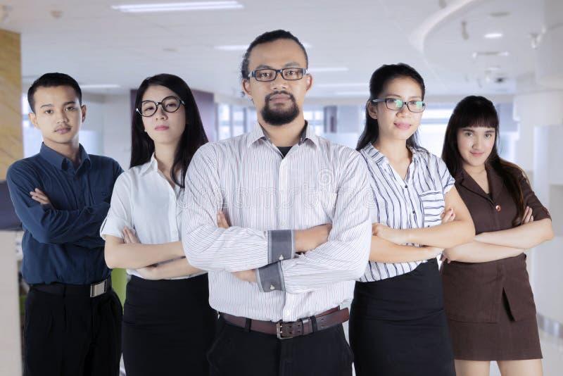 Groep zekere vijf bedrijfsmensen met zakenmanleider bij voorzijde royalty-vrije stock afbeeldingen