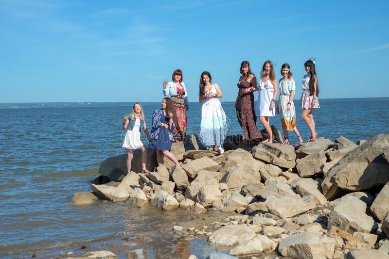 Groep zich het verenigen van jonge hippievrouwen bij een strand op een de zomerdag Gelukkige jongeren die van een dag genieten bi royalty-vrije stock afbeelding