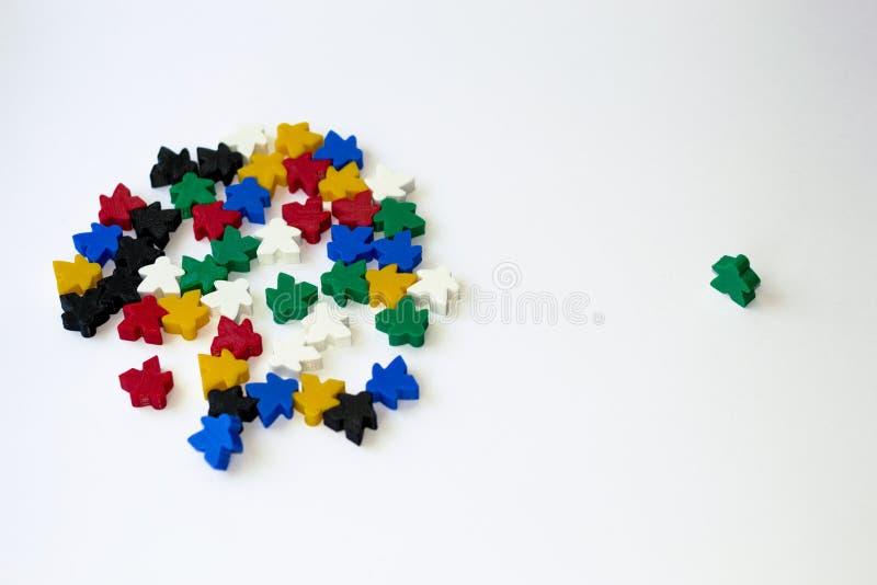 Groepen kleurrijke die meeples op witte achtergrond wordt geïsoleerd Blauw, rood, zwart, groen en geel Kleine cijfers van de mens stock afbeeldingen