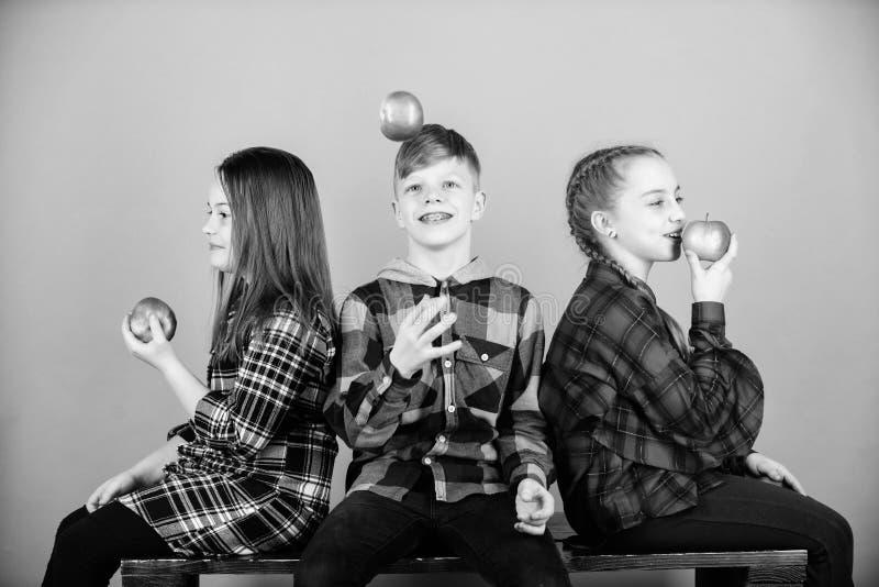 Groeperige tieners die appels communiceren en eten Jongen en meisjes vrienden eten appelsnack terwijl ze ontspannen Teens royalty-vrije stock foto