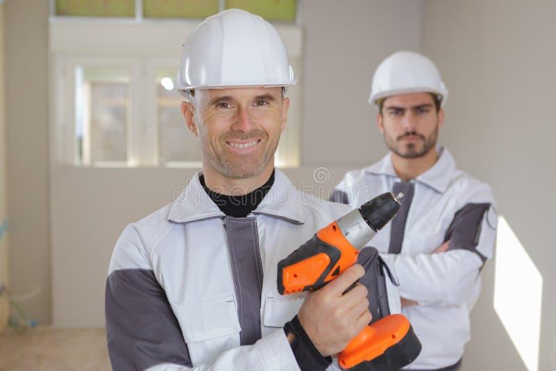 Groeps glimlachende bouwers in bouwvakkers met elektrische boor binnen royalty-vrije stock foto
