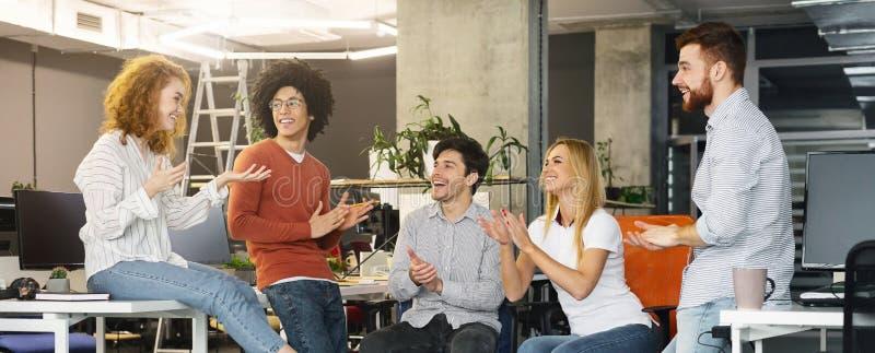 Groeps multi-etnische bedrijfsmensen die aan nieuw lid van team toejuichen royalty-vrije stock afbeeldingen