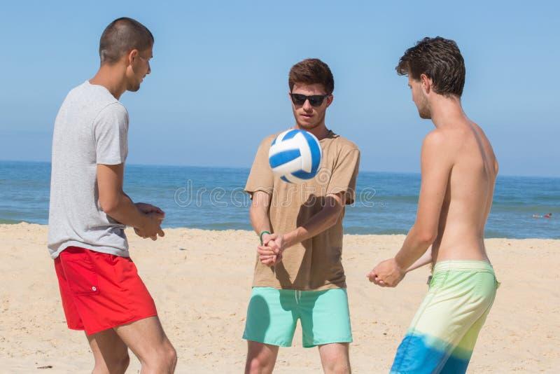 Groeps tienervrienden die volleyball op strand spelen stock foto's
