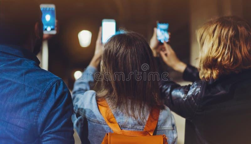 Groeps volwassen hipsters samen gebruikend in handen mobiele telefoonclose-up, het online concept van WiFi Internet in straat, bl stock afbeelding