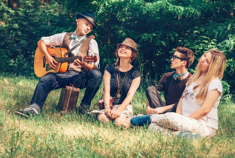 Groeps zingende tieners op de bosopen plek stock afbeeldingen