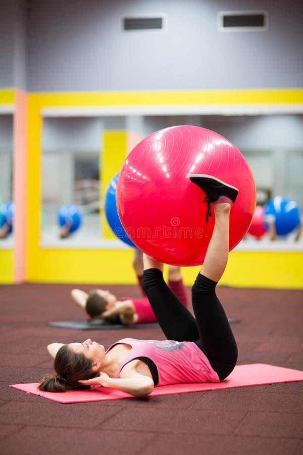 Groepsmensen in een pilatesklasse bij de gymnastiek stock afbeeldingen