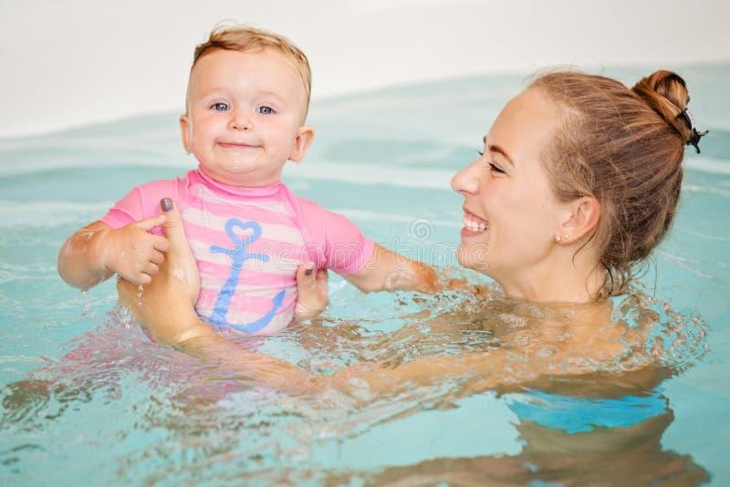Groepsportret die van het witte Kaukasische moeder en babydochter spelen in water die in zwembad binnen duiken, in camera, tra ki stock foto