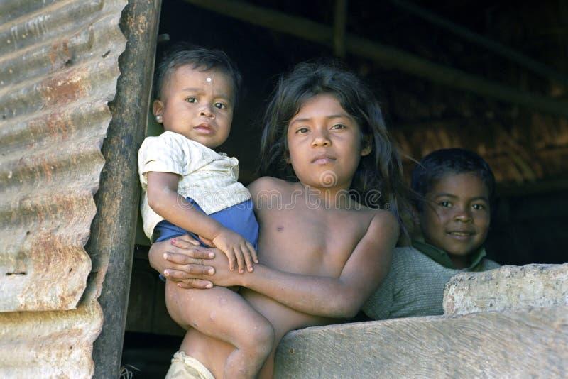 Groepsportret van Indische kinderen in deuropeningshut stock foto
