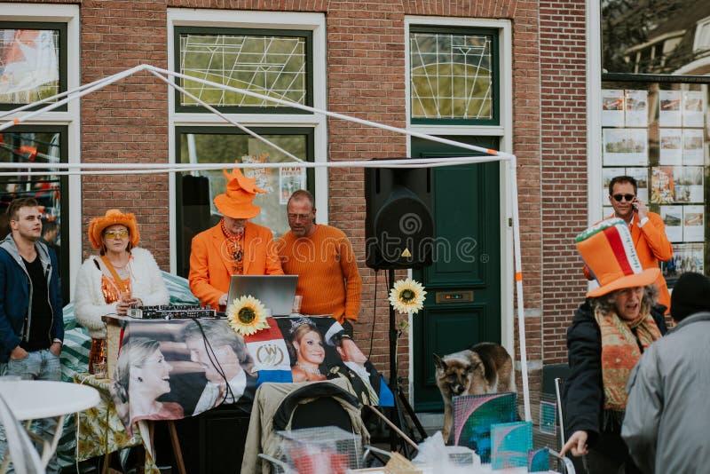 Groepsportret van mensen in oranje, gekke blik, straatactiviteiten voor de festiviteit van de Konings` s Dag in Nederland stock afbeelding