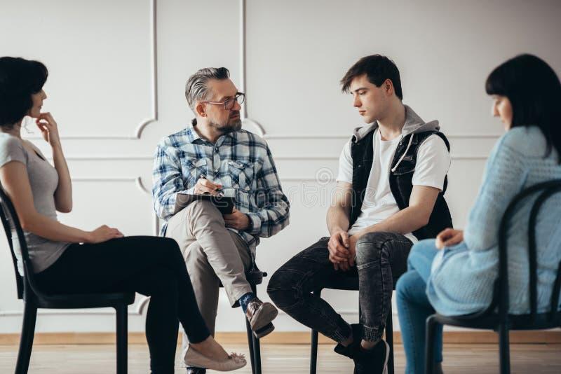 Groepstherapie met psycholoog en de gedeprimeerde mens en vrouw stock foto's