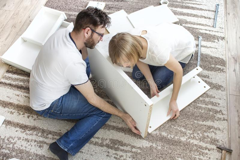 groepswerk De echtgenoot en de vrouw verdraaien samen het meubilair in de woonkamer, aanpassend de houten elementen van de meubil royalty-vrije stock fotografie