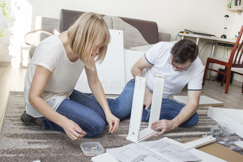 groepswerk De echtgenoot en de vrouw verdraaien samen het meubilair in de woonkamer, aanpassend de houten elementen van de meubil stock afbeelding