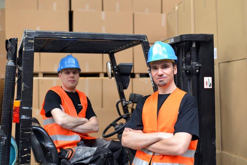 Groepswerk in logistiek - groep arbeiders in een warenhuis w stock afbeelding