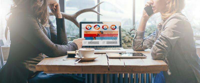 Groepswerk, twee jonge onderneemsters die over lijst van elkaar zitten Voor lijstlaptop, koffiekop en tabletcomputer royalty-vrije stock afbeelding