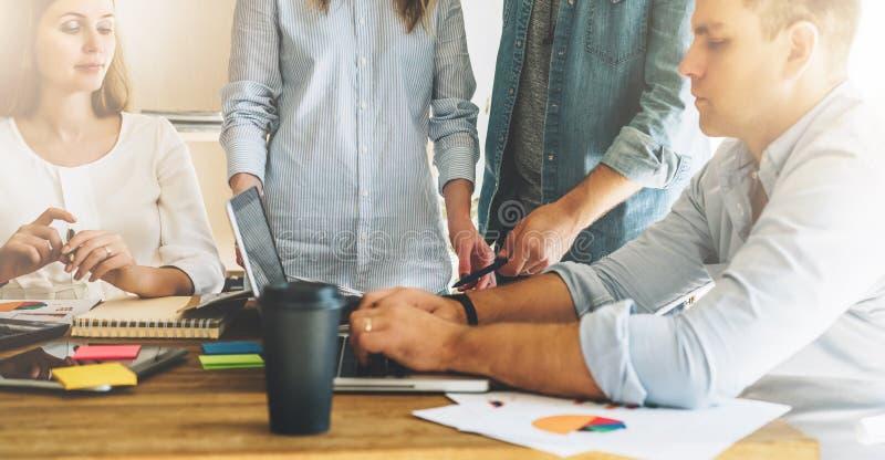 Groepswerk, uitwisseling van ideeën De groep jong zakenlui werkt in bureau samen bij lijst, lezend document documenten stock fotografie