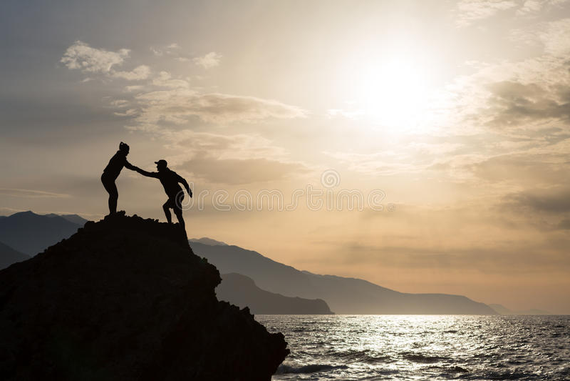 Groepswerkpaar beklimmen die met het helpen van hand wandelen stock afbeelding