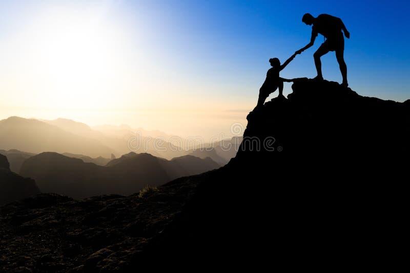 Groepswerkpaar die helpend hand wandelen stock foto