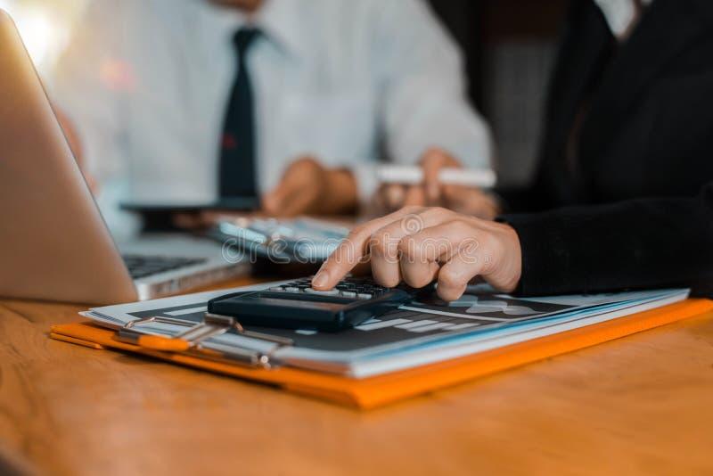 Groepswerkproces, Commercieel team die een calculator gebruiken om de aantallen statistiek bedrijfswinstengroeipercentage op docu stock foto's