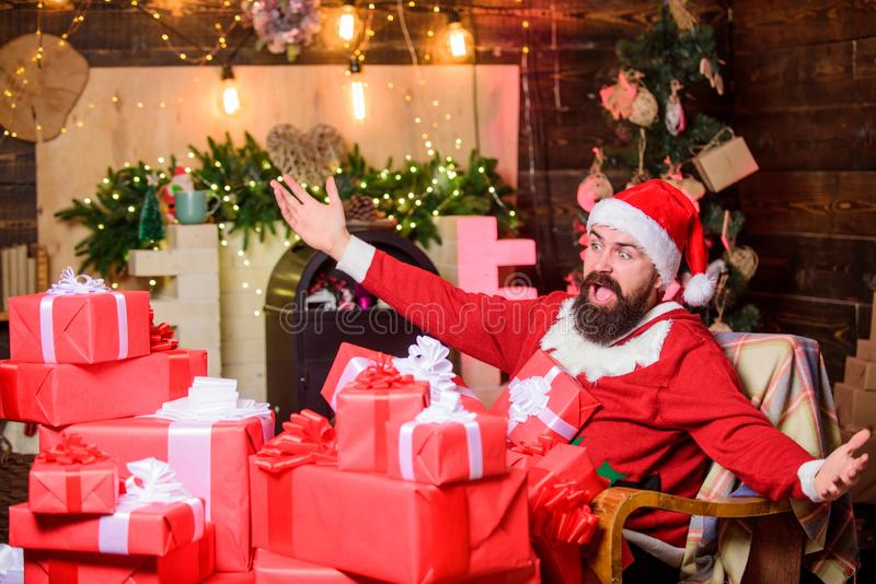 Groeten van Santa Bearded man zit in een stoel met een hoop geschenken Verblijfplaats van Santa claus Wintervakantie Cozy home royalty-vrije stock afbeeldingen