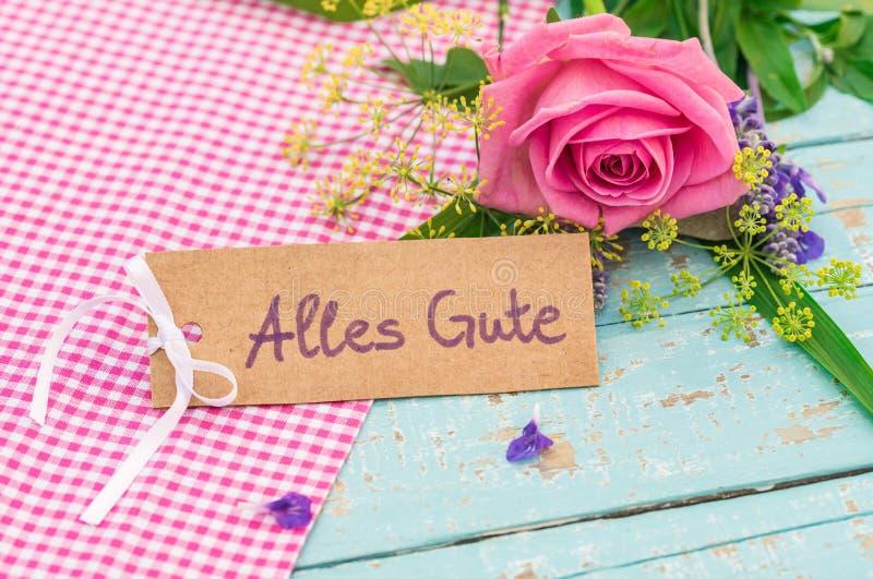 Groetkaart met Duitse teksten, Alles Gute, middelenbeste wensen en romantische bos van bloemen stock afbeeldingen