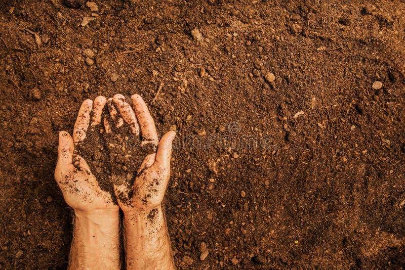 Grond in de handen van de landbouwers` s mens ` s op gebiedsachtergrond royalty-vrije stock foto