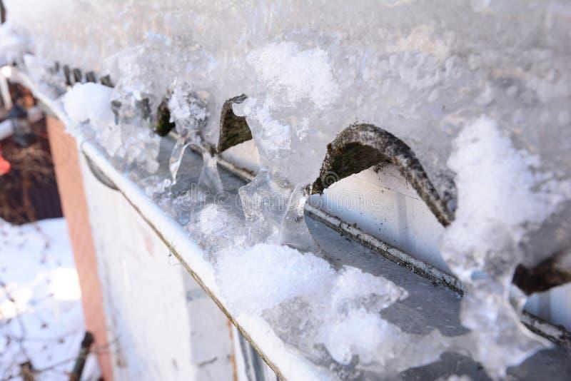 Grondaia della pioggia in pieno di ghiaccio nell'inverno Ghiaccio congelato in grondaia del tetto della casa fotografia stock libera da diritti