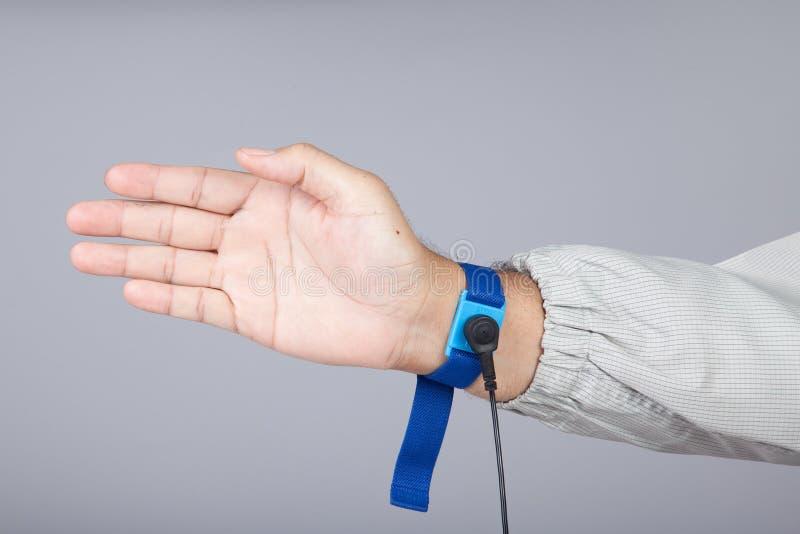 Grondarmband op mensenhand die ESD doek grijze achtergrond dragen A stock foto's