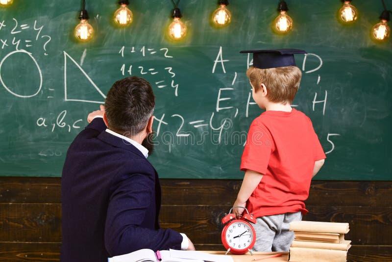 Grondbeginselen van onderwijsconcept De jongen, kind in gediplomeerd GLB bekijkt gekrabbel op bord terwijl de leraar verklaart le stock foto's