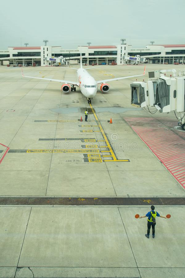 Grondbemanning die een inkomend vliegtuig leiden in positie stock foto