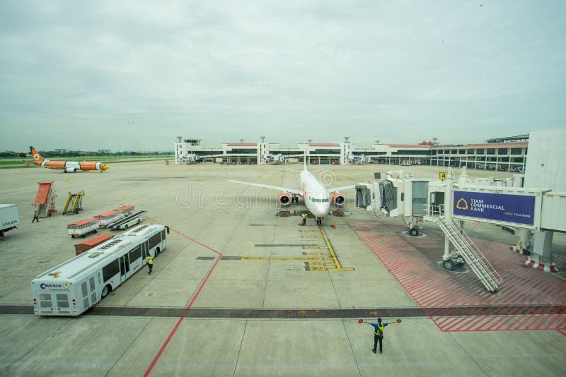 Grondbemanning die een inkomend vliegtuig leiden in positie stock afbeelding