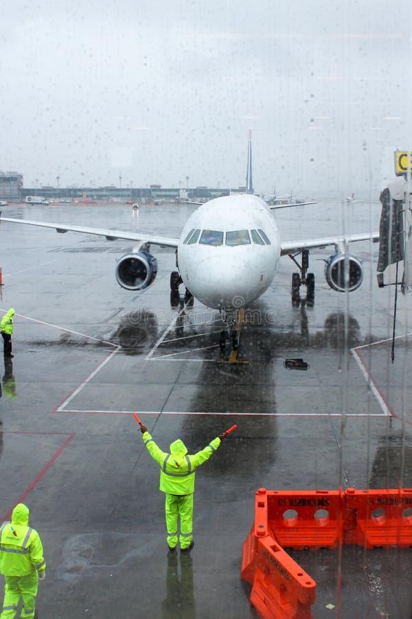 Grondbemanning die een inkomend vliegtuig leiden in positie om een straal-manierbrug te ontmoeten stock afbeelding