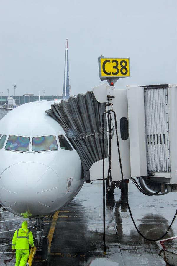 Grondbemanning die een inkomend vliegtuig leiden in positie om een straal-manierbrug te ontmoeten stock foto's