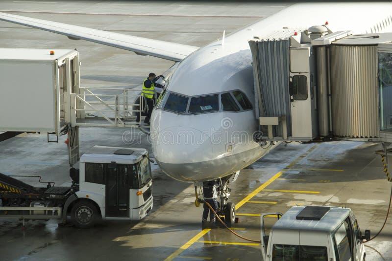 Grondbemanning die en onder een passagiersvliegtuig bijtanken werken stock fotografie