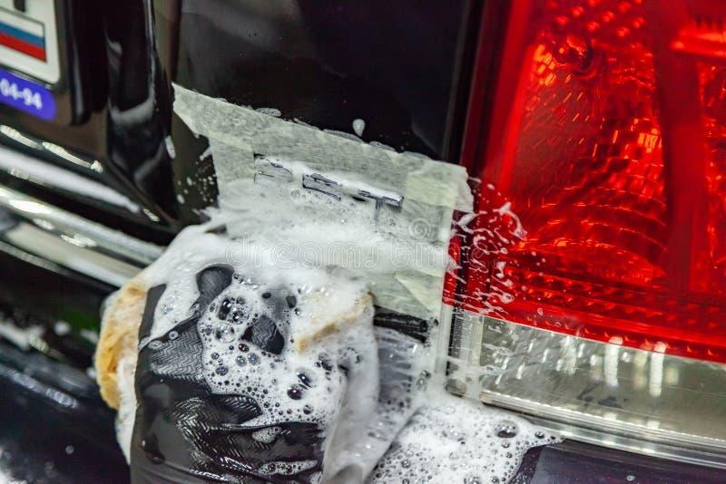 Grondige en nauwgezette was van autodelen in de vorm van emblemen in een zwarte handschoen met een spons en wit schuim in het voe royalty-vrije stock foto
