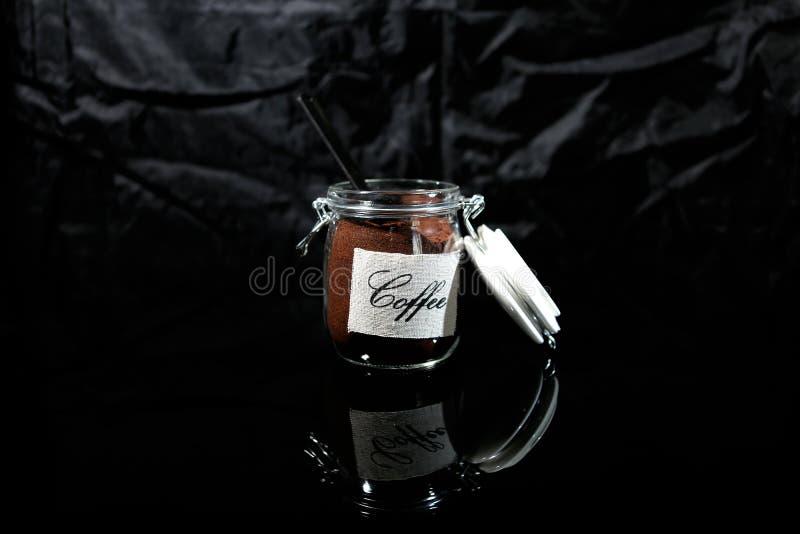 Grondkoffie in een glaskruik stock foto