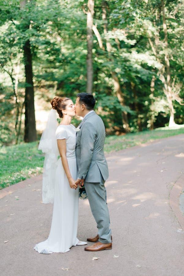 Groom брюнет в сером костюме целует предложение невесты в ярком лете стоковое фото rf