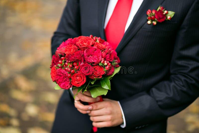 Groom держа bridal конец букета вверх красные розы сада украшенные в составе стоковые изображения rf