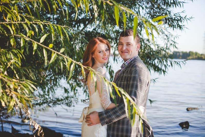Groom и невеста на речном береге стоковые фотографии rf