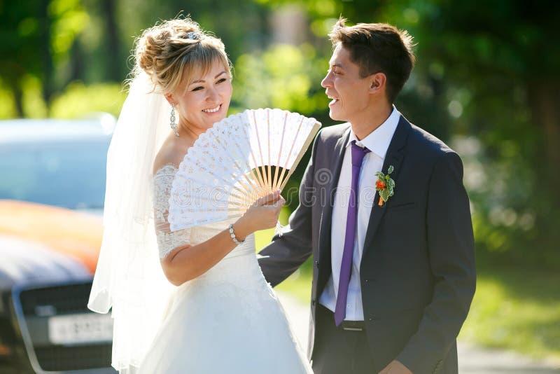 Groom и невеста с вентилятором на улице загоренной солнцем, автомобилем в предпосылке стоковая фотография