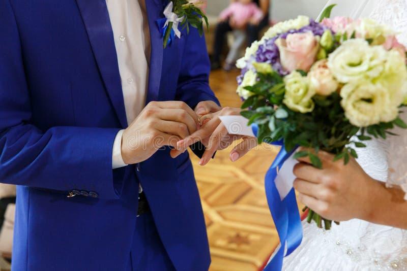 Groom кладя кольцо на палец невесты стоковое изображение