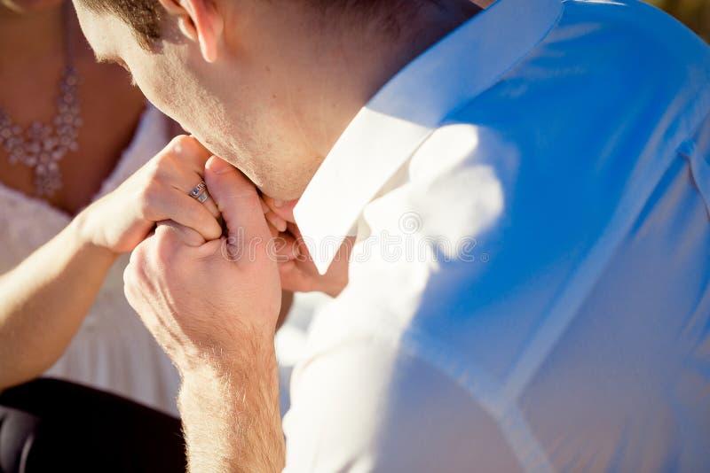 Groom нежно целует конец руки невесты вверх стоковое изображение