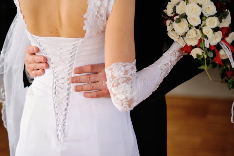 Groom обнимает невесту, корсет невесты стоковая фотография rf