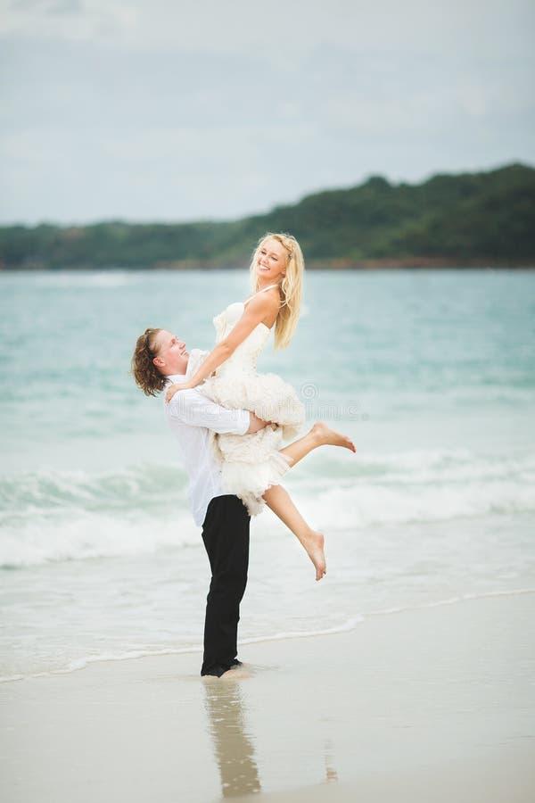 Groom поднял его невесту от моря счастливые новобрачные на дезертированном пляже стоковое фото