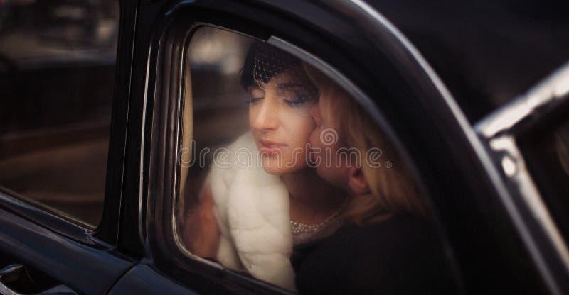 Groom целует невесту на заднем сиденье старого винтажного автомобиля стоковые фотографии rf
