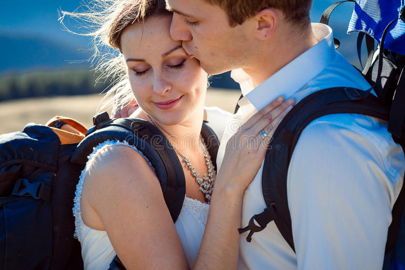 Groom целует его очаровательный конец невесты вверх Высокогорные горы на предпосылке стоковая фотография rf