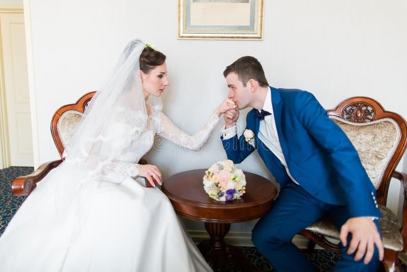 Groom целует руку невесты в красивом интерьере стоковые фото
