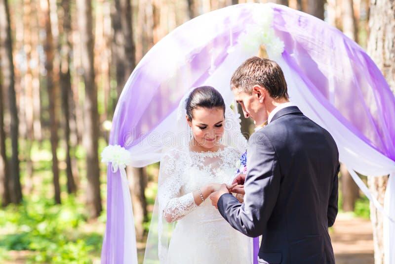 Groom элегантности кладя на обручальное кольцо его невесту венчание цветка церемонии невесты стоковое фото rf