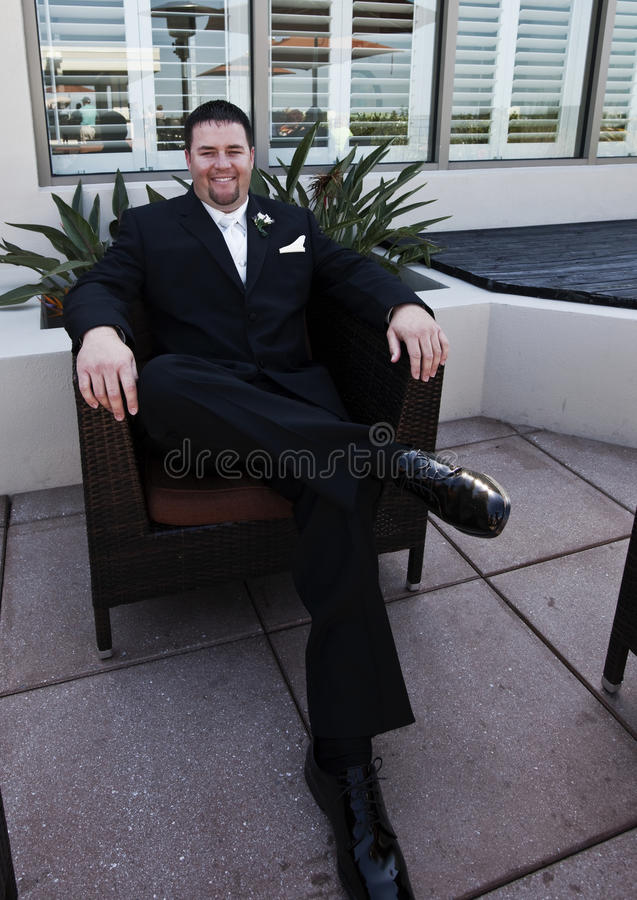 Groom. A smiling handsome groom wearing black tuxedo sitting on patio royalty free stock photo