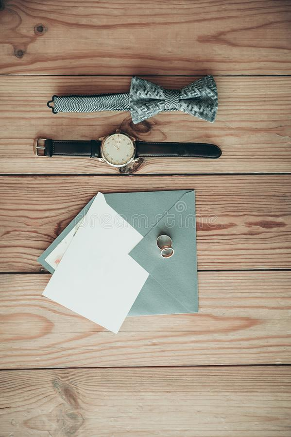 Groom accessories for wedding day – watch, bow tie, rings, envelope with copy space card royalty free stock images